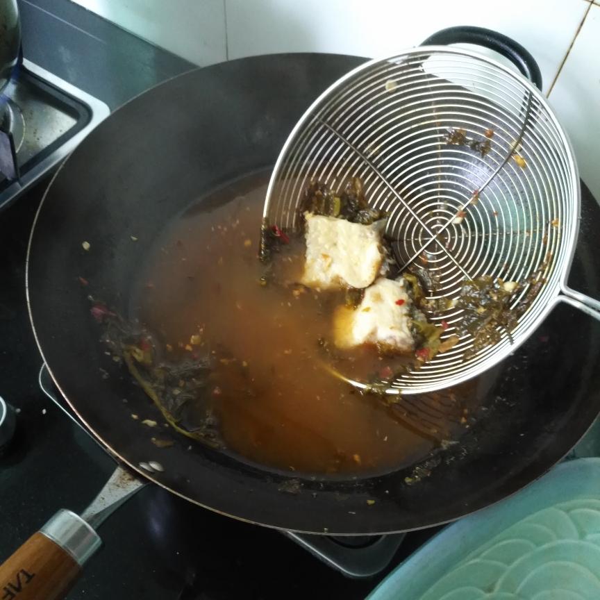 捞出鱼骨和酸菜,放碗里,备用。