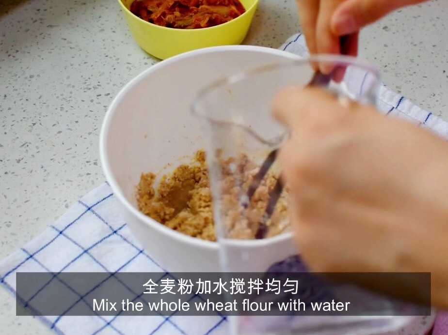 将水缓缓加入全麦粉中搅拌均匀