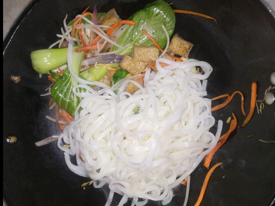 配菜炒差不多了就将米皮加入,翻炒均匀后把酱汁倒入,翻炒均匀。