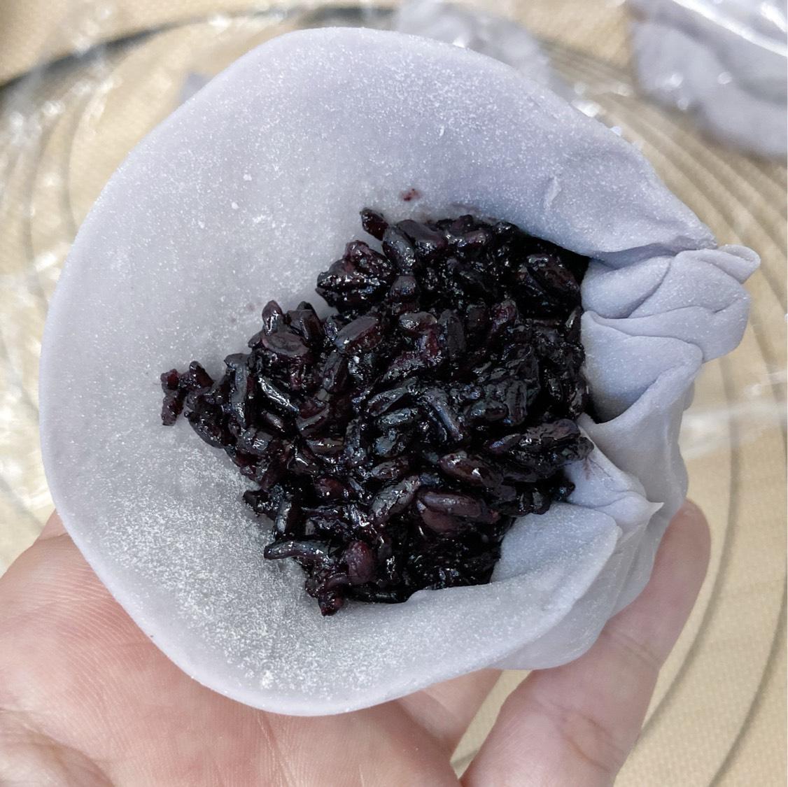 将紫米放入面团中包好,收口朝下